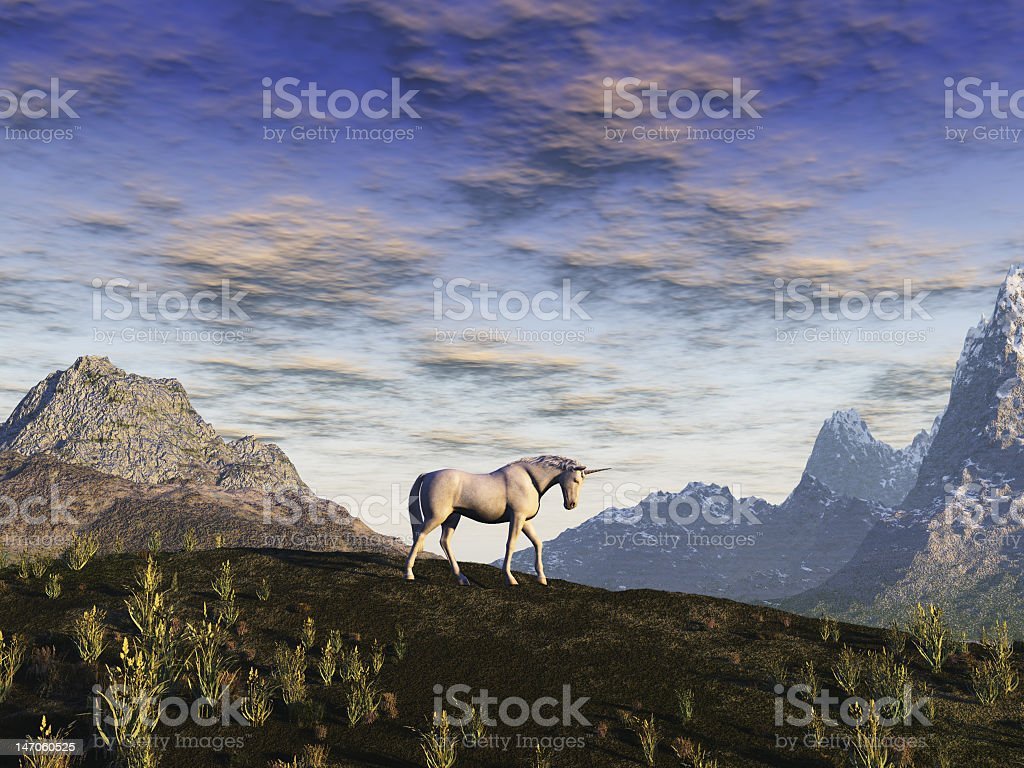 Lone unicorn in a field with mountains in the background stock photo