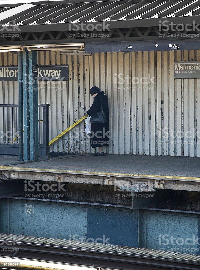 Lone donna alla stazione ferroviaria foto stock royalty-free