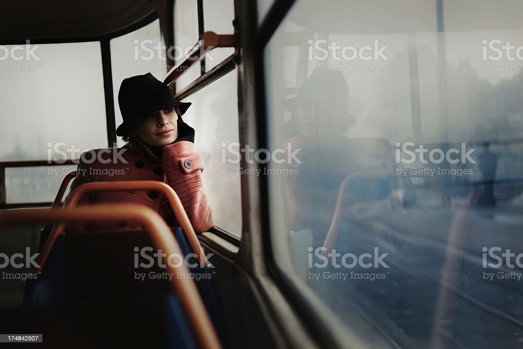 Lone woman in a train car looking off into the distance stock photo