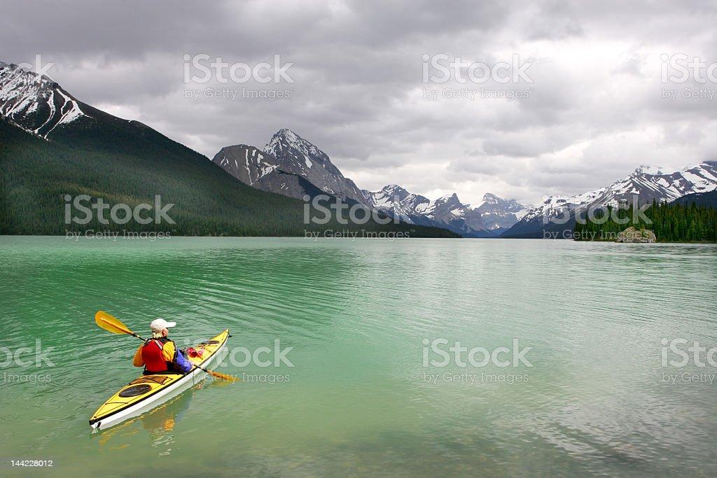 Lone woman in yellow kayak at Banff's Lake Louise royalty-free stock photo