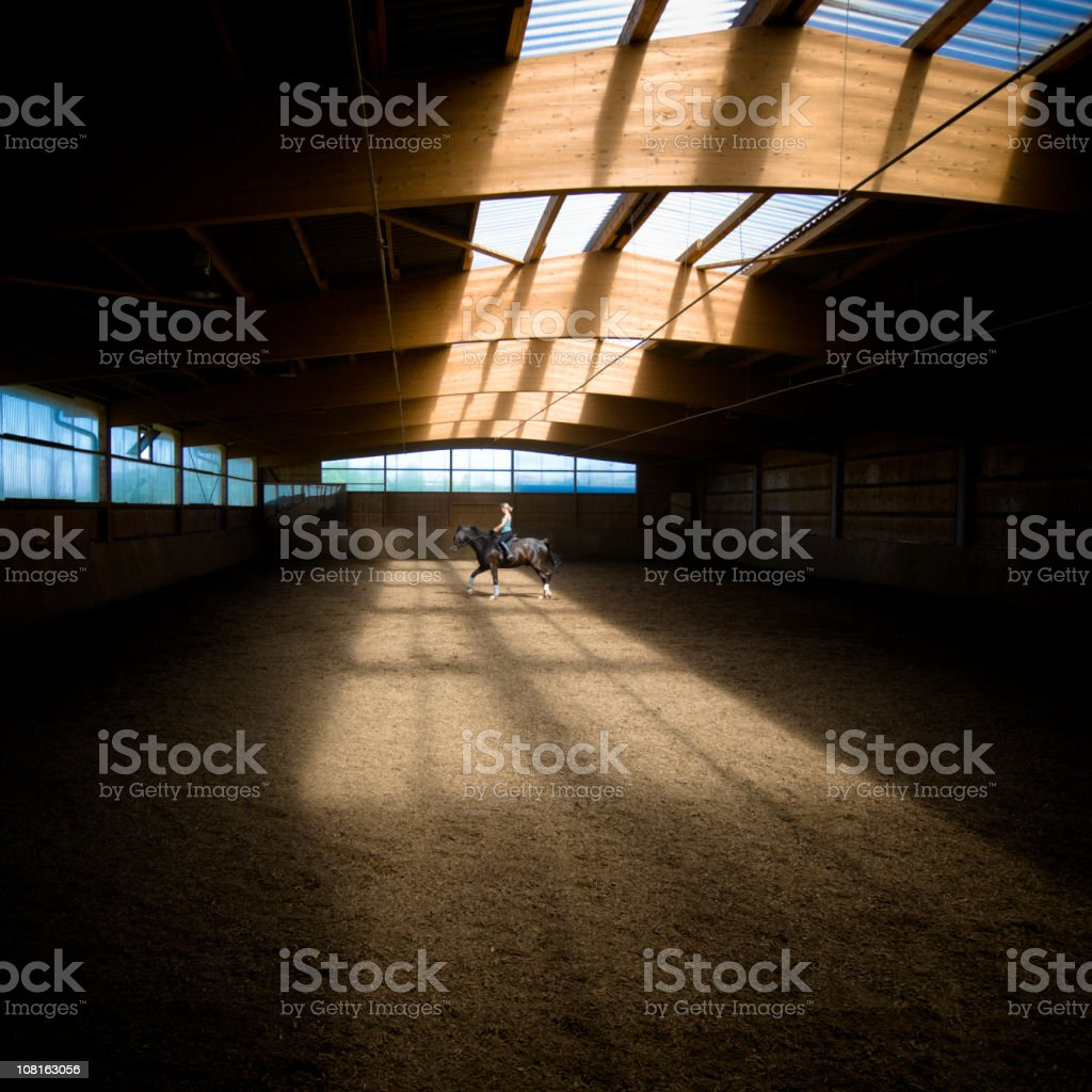 Lone Woman Riding Horse in Indoor Ring royalty-free stock photo