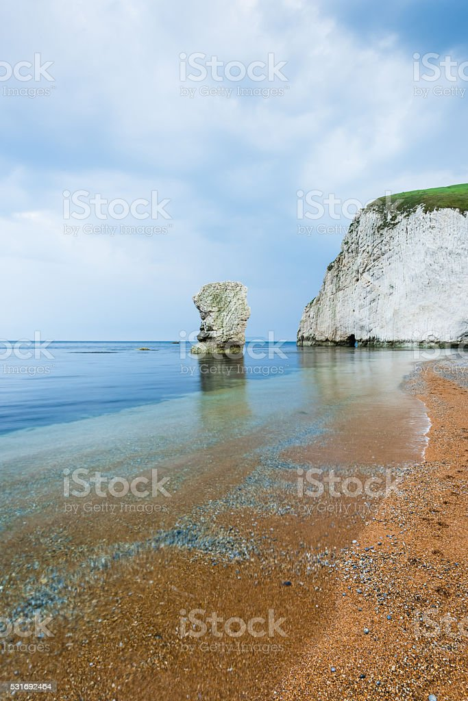 lonelly rock formation at coastline in Dorset stock photo