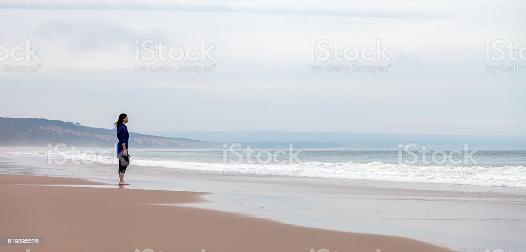 Lonely and depressed woman watching the sea stock photo