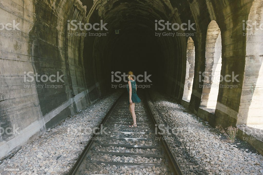 Lonely attractive, blond girl inside of dark railroad tunnel stock photo