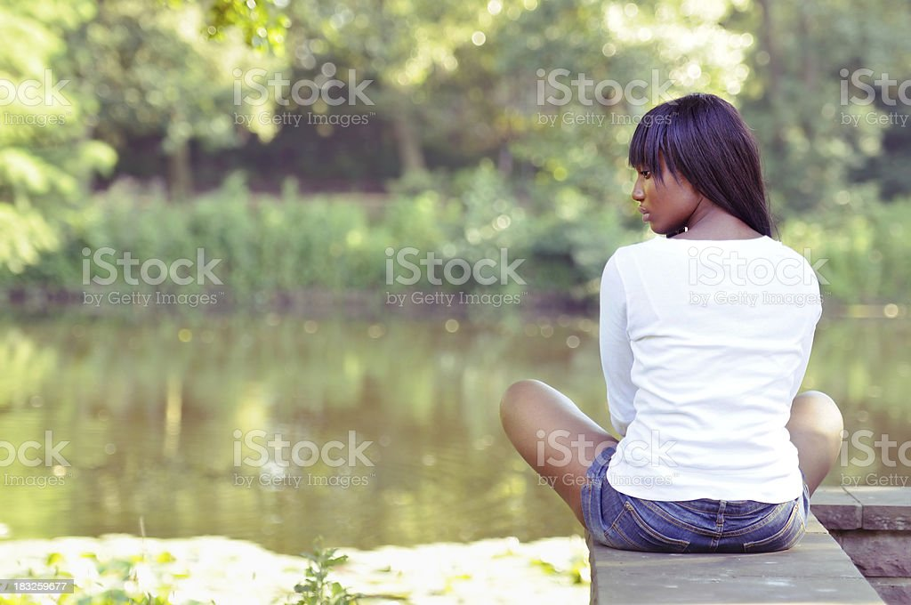 Lonely beautiful ethnic woman sitting at a park royalty-free stock photo