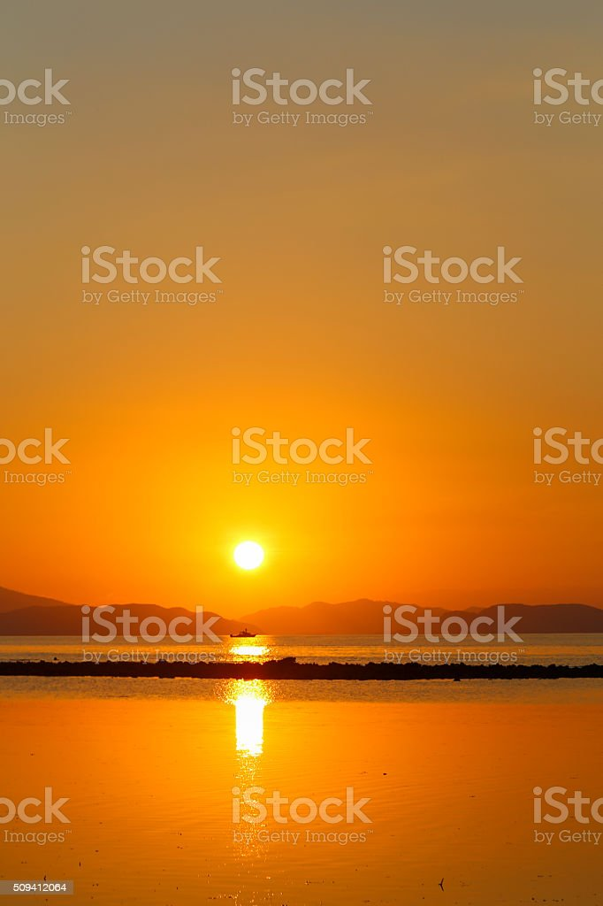 Lonely boat in the Flores sea at sunset. stock photo