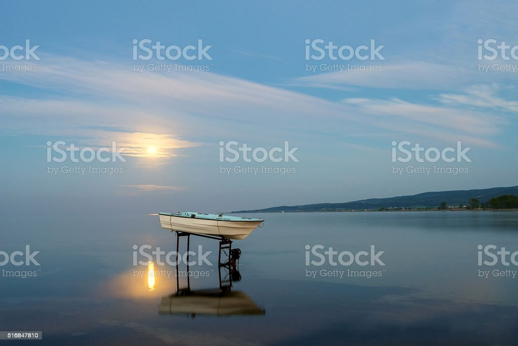 Lonely boat in the moonlight stock photo