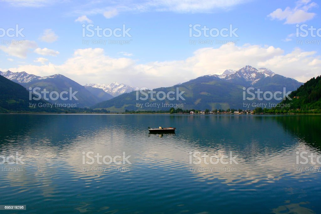 Lonely boat on Beautiful Zeller lake - Zell am See and Mountain range landscape, Tirol landscape in Austrian Salzburger land, Austria stock photo