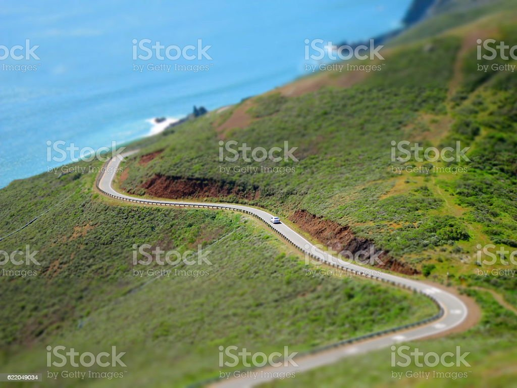 lonely car driving down a road by the ocean stock photo