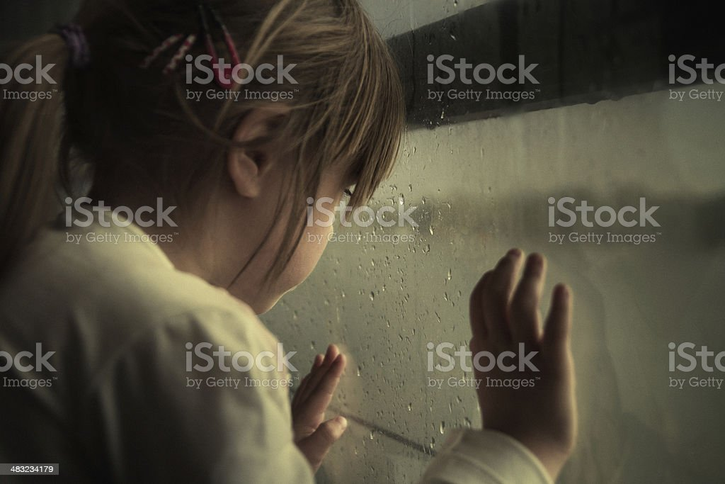 Lonely child looking through window stock photo