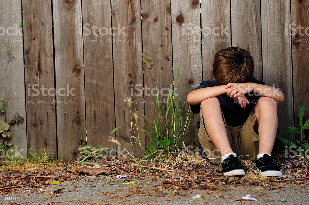 A lonely child sitting by himself outdoors royalty-free stock photo