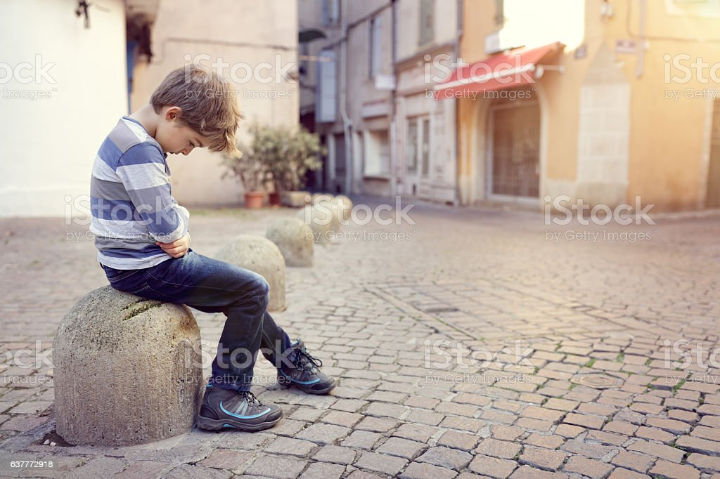 Lonely child sitting on a street corner stock photo
