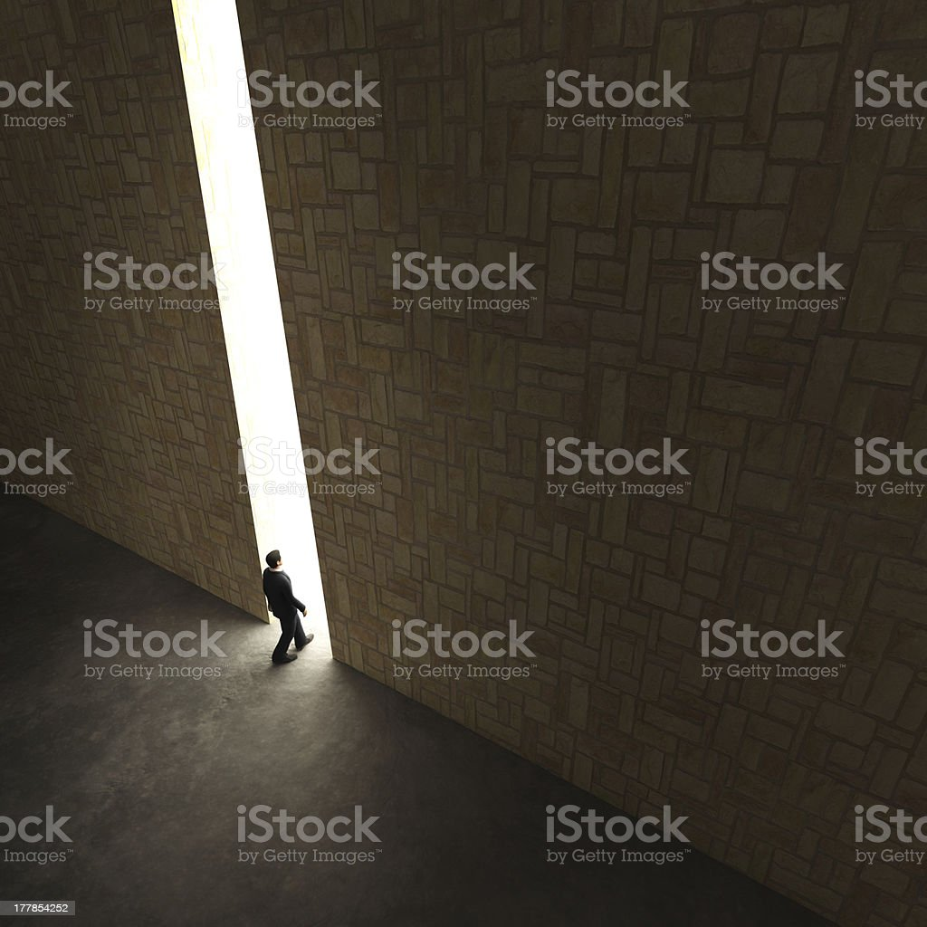 Lonely explorer walks through small gap in tall stone wall stock photo