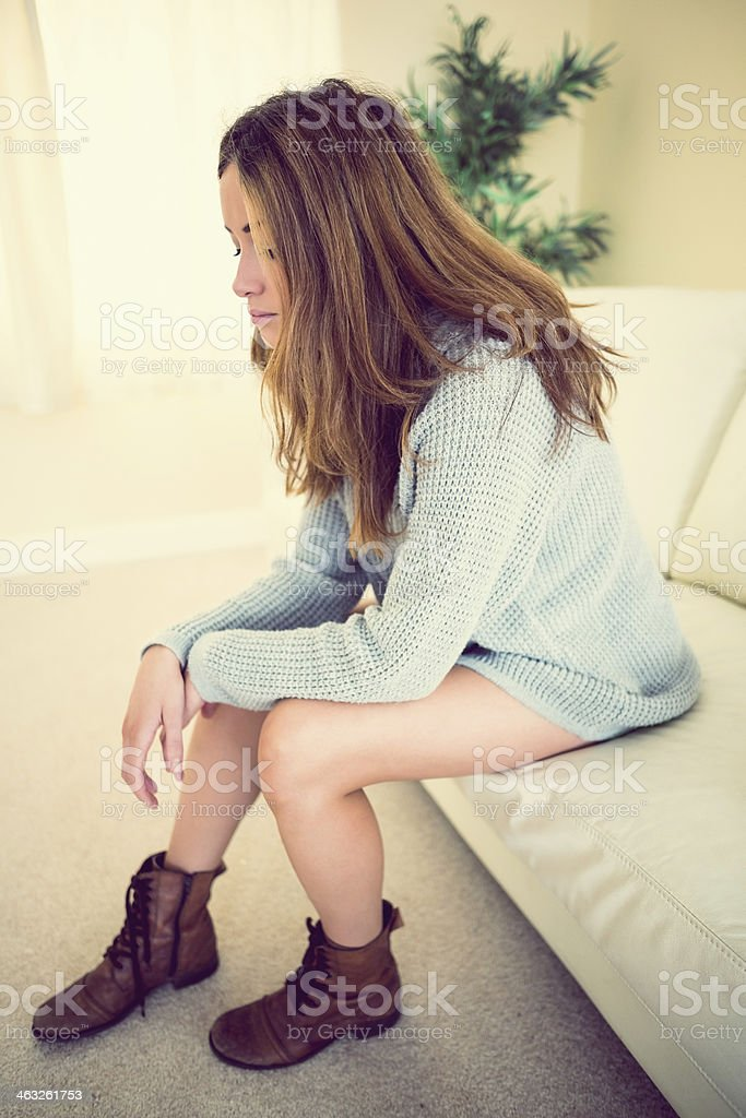 Lonely fashionable woman sitting on couch royalty-free stock photo