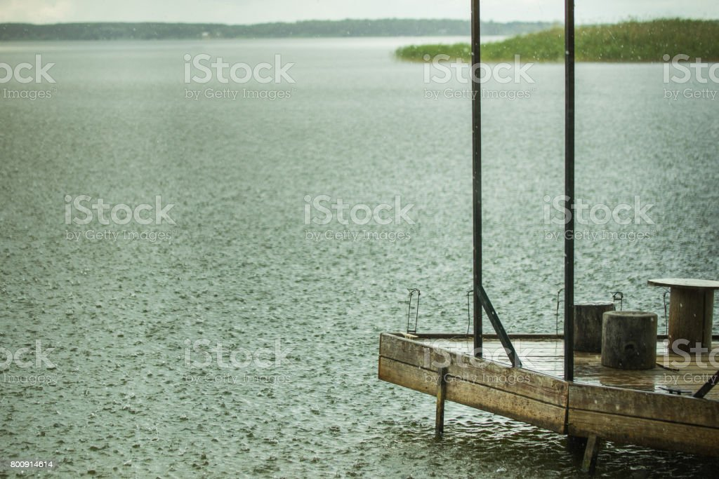 Lonely fishing pier on a lake under heavy shower rain. Bad weather....