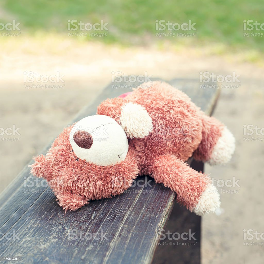 Lonely forgotten teddy bear toy lying on the bench. stock photo