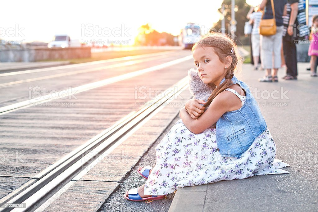 Lonely girl on a city tram station stock photo