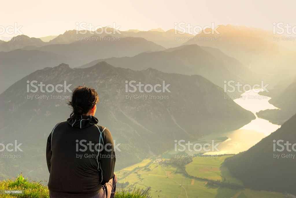 Lonely Girl on the top of a mountain looking down stock photo