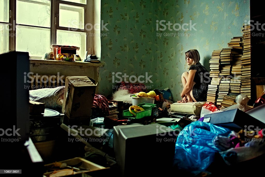 Lonely girl sitting in a room littered with things stock photo