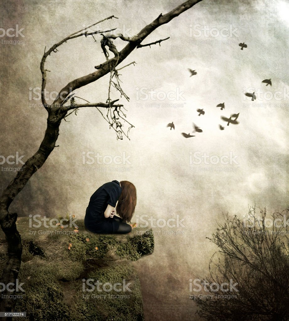 Lonely girl sitting on a rock in sorrow stock photo