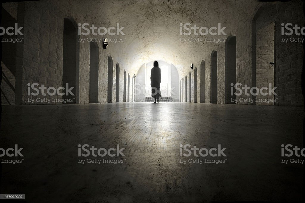 Lonely girl walking down a hallway stock photo