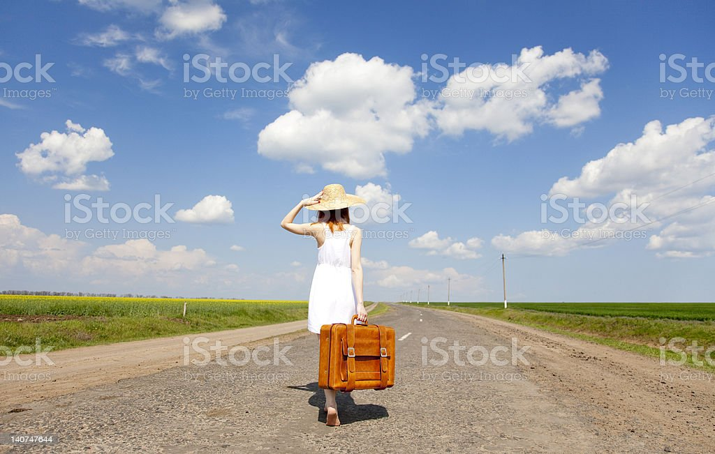 Lonely girl with suitcase at country road. royalty-free stock photo