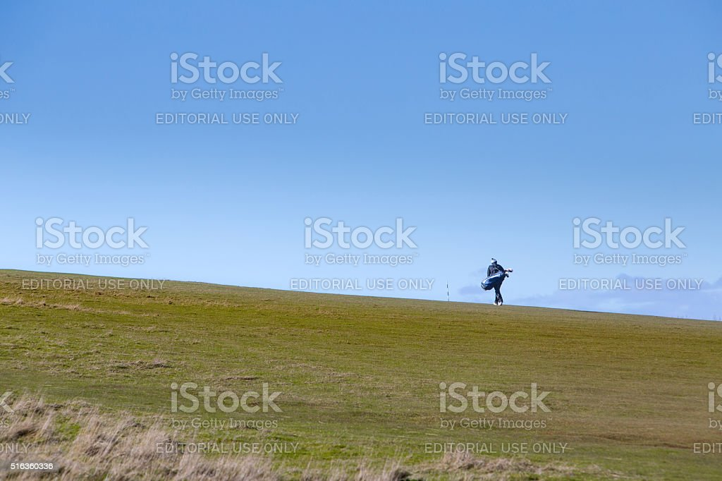 Lonely golfer walking up a hill stock photo