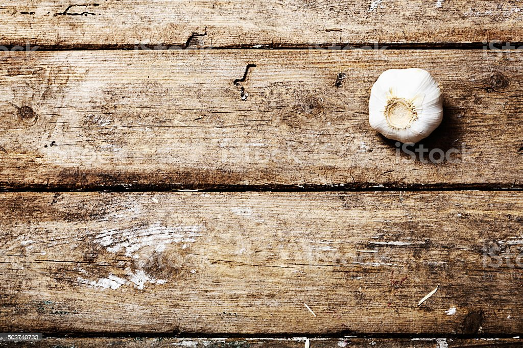 Lonely head of garlic on weathered wood: the anti-social vegetable stock photo
