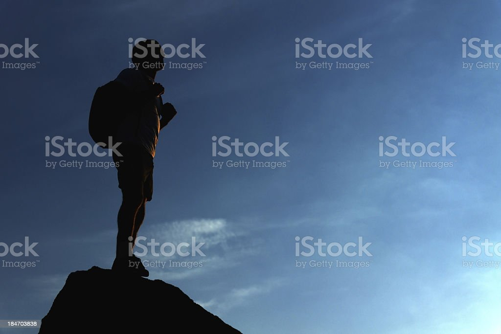 Lonely male hiker standing on the mountain top stock photo