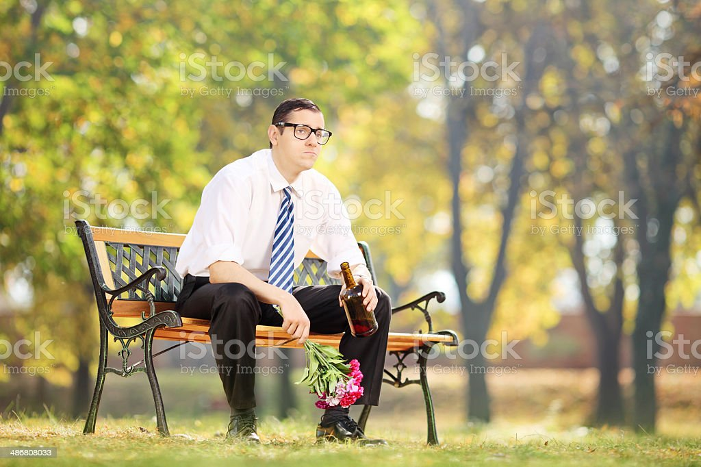 Lonely man drinking alcohol in park stock photo