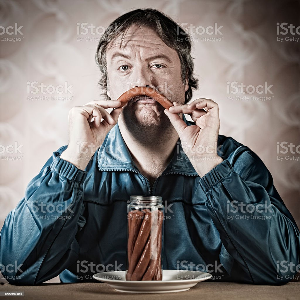 Lonely man eating in dingy enviroment. stock photo