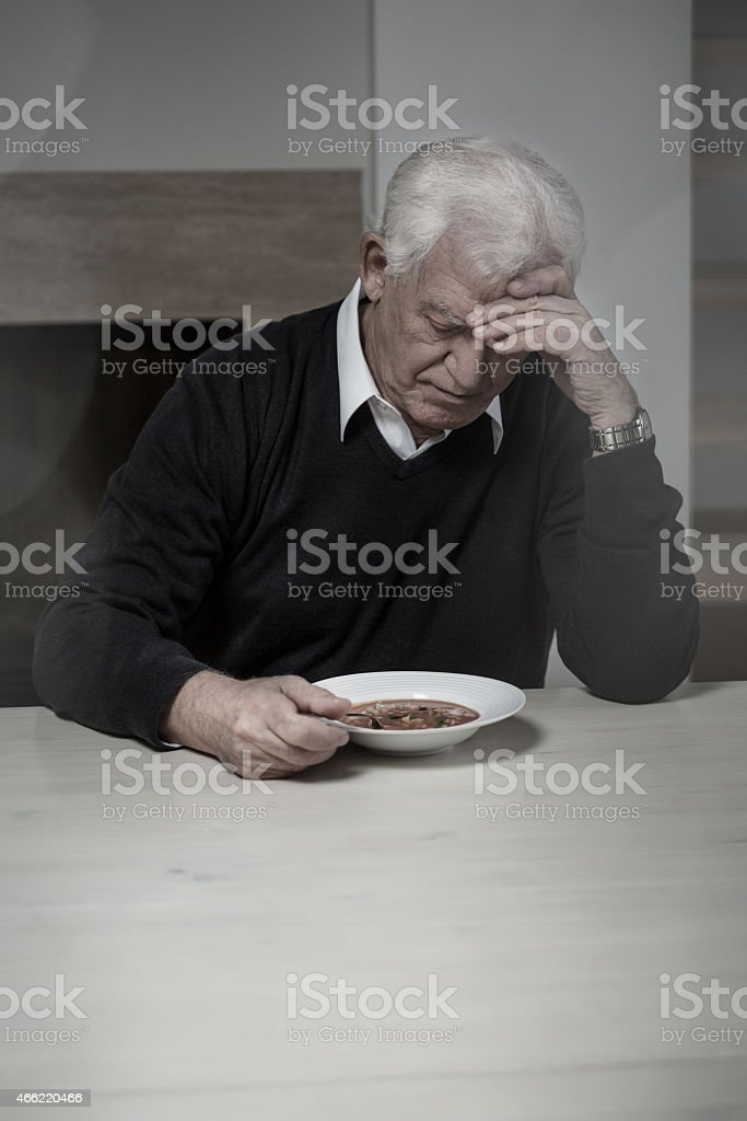 Lonely man eating soup stock photo