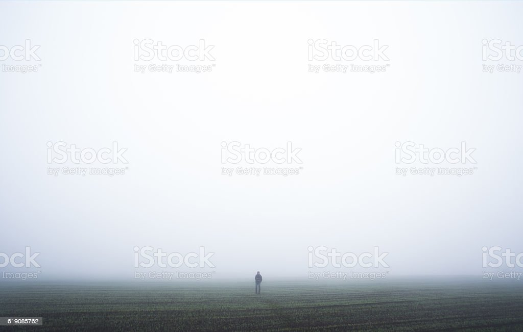 Lonely man in a fog stock photo