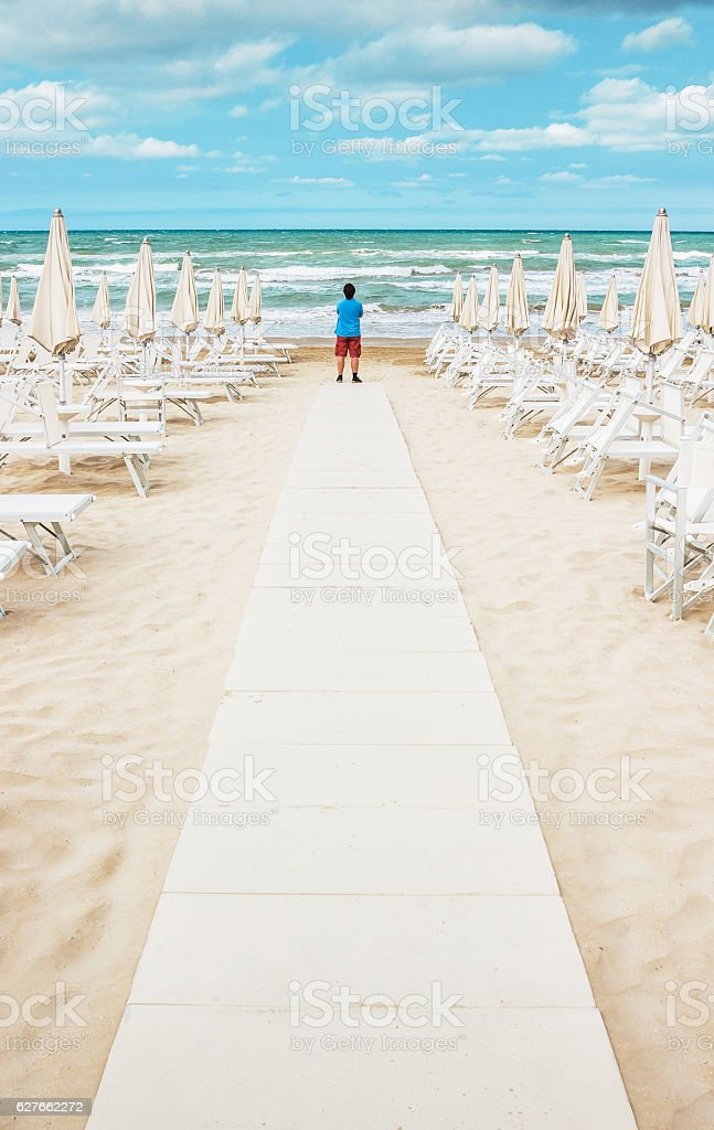 Lonely man is standing on the empty beach stock photo