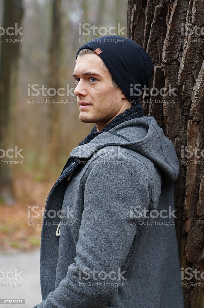 lonely man leaning against a tree stock photo