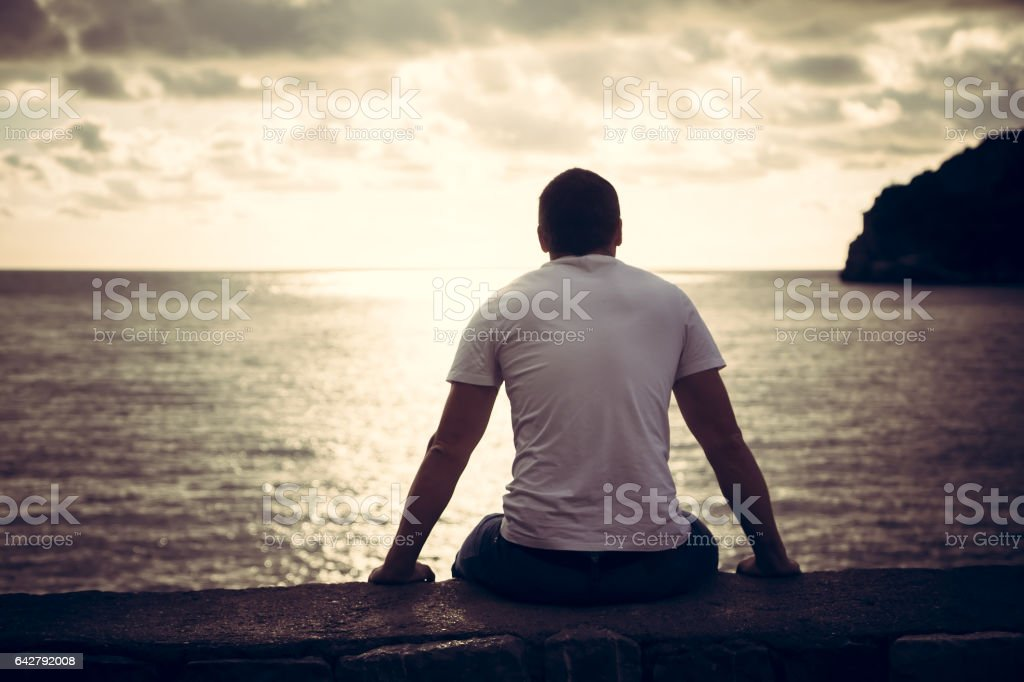 Lonely man looking with hope at horizon with sunlight during sunset with effect of light at the end of tunnel stock photo