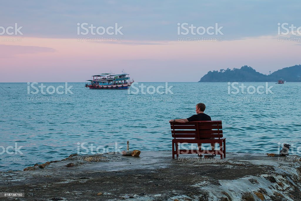Lonely man sits on a bench on the coast stock photo