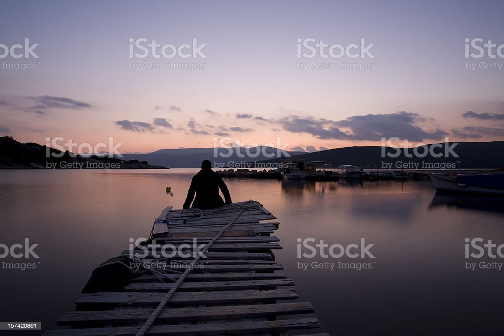 lonely man sitting side of the dock royalty-free stock photo