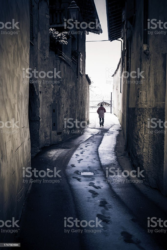 Lonely Man Walking in Alley while Snowing royalty-free stock photo