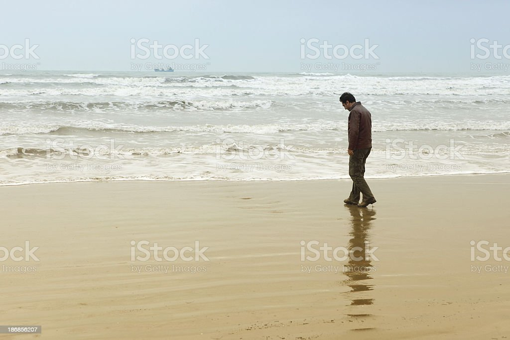 Lonely man walking on a beach in Durres, Albania royalty-free stock photo