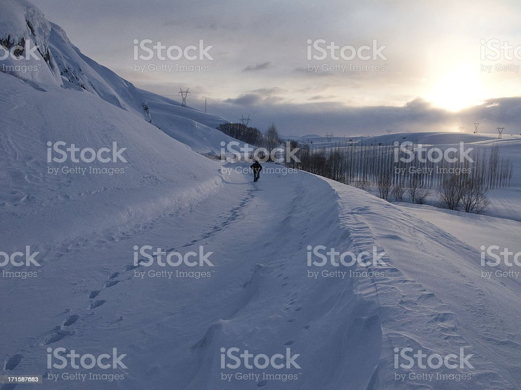 Lonely man walking on snow in sunset stock photo