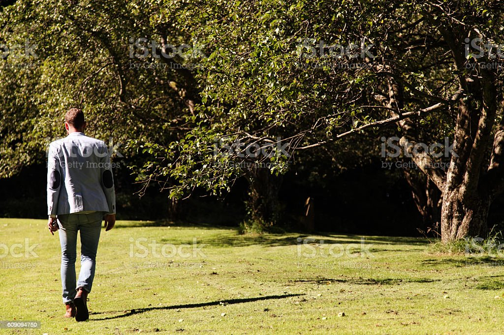 Lonely man walking outdoors in the sunlight stock photo