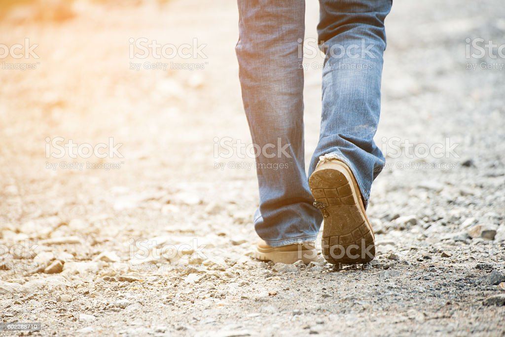 Lonely man wearing jeans and leather boots walking stock photo