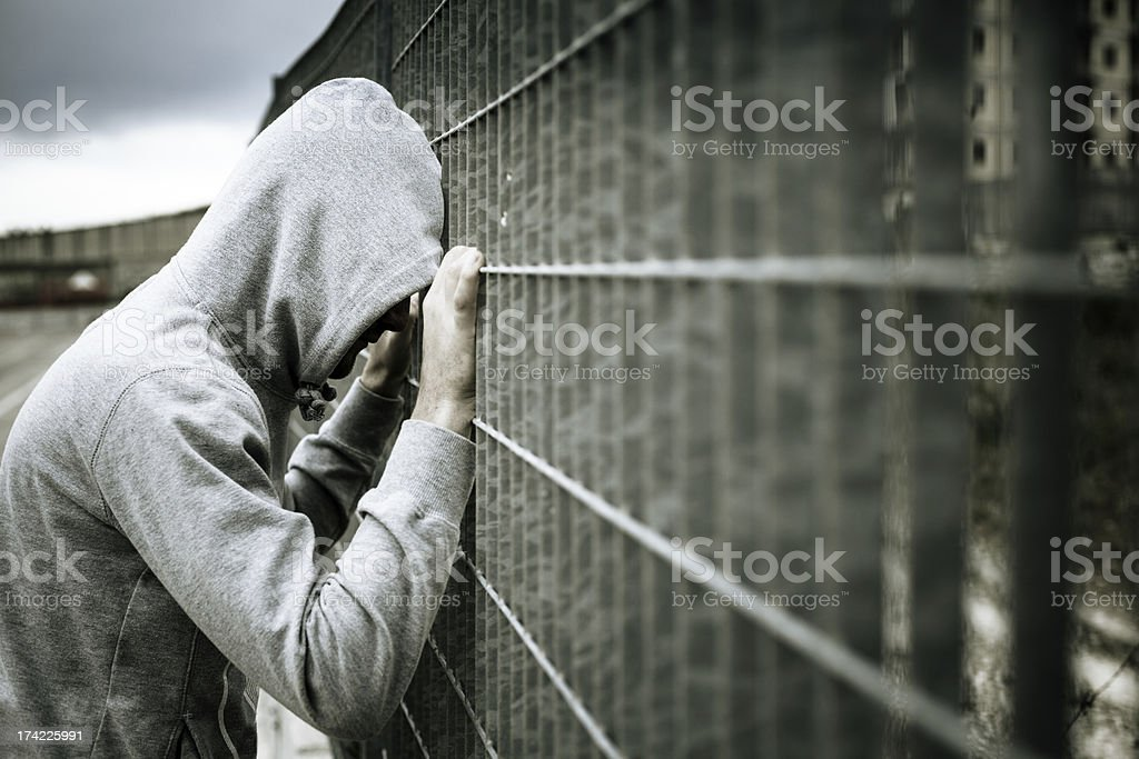 Lonely Man with Hood Leaning on a Fence stock photo