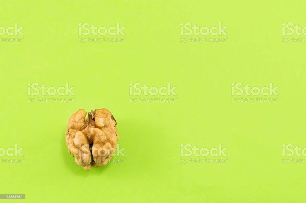 Lonely peeled walnut on green background stock photo
