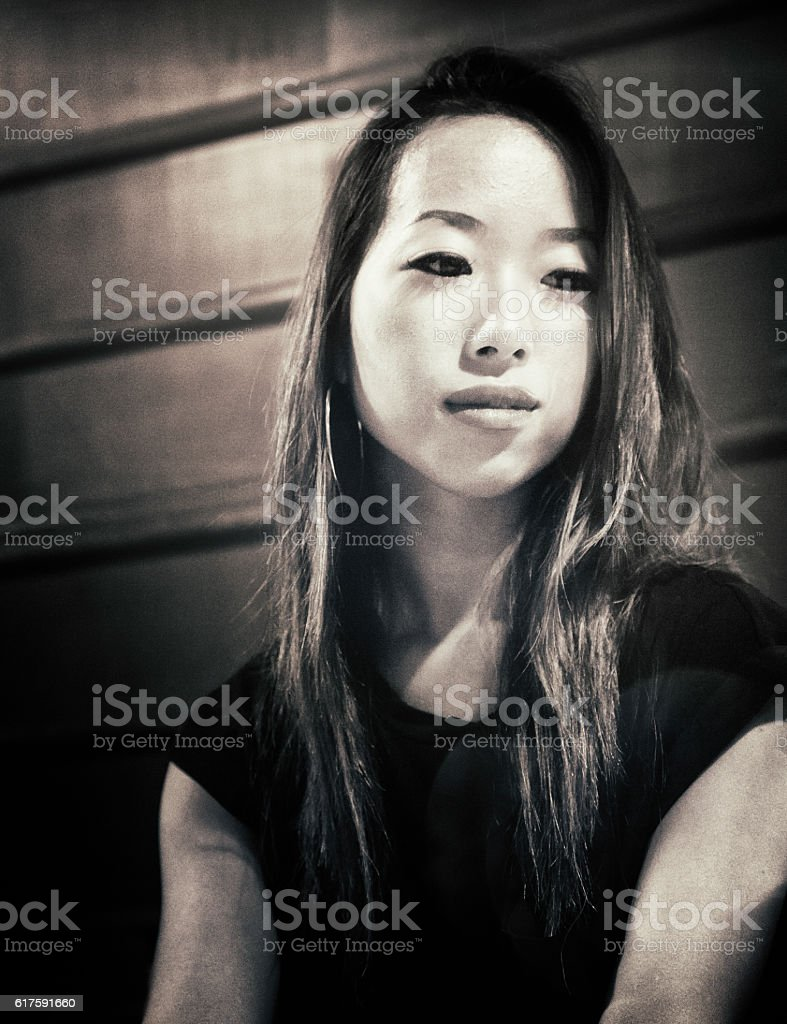 Lonely pensive young Japanese woman looking down stock photo