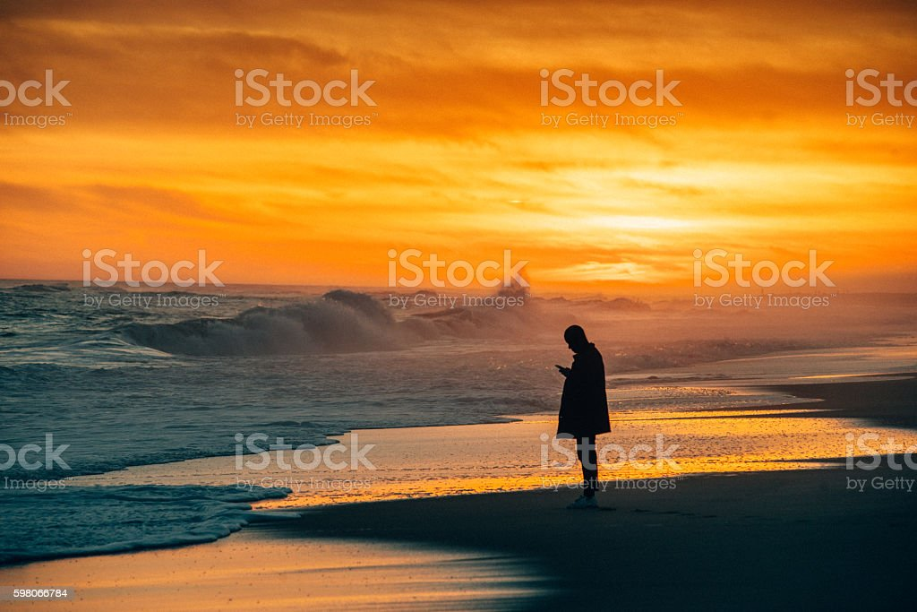 Lonely person using smartphone at the Beach stock photo