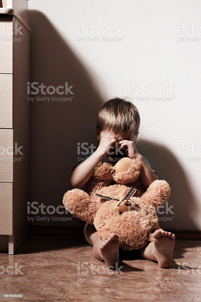 Lonely sad boy crying in corner, holding toy bear stock photo