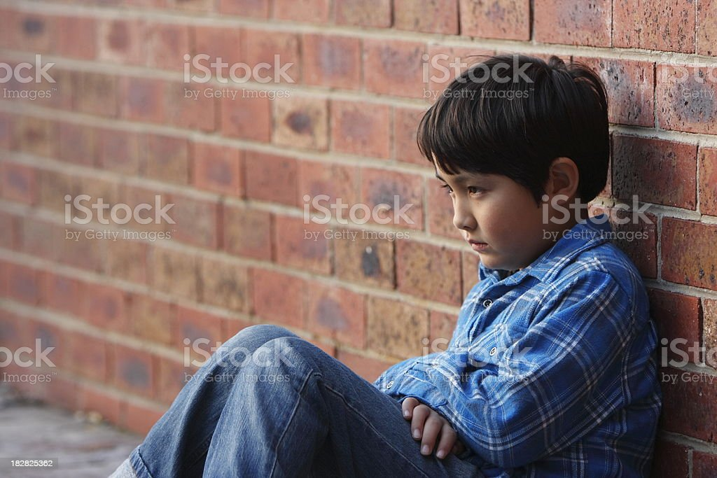 Lonely school aged boy slumped against brick wall royalty-free stock photo