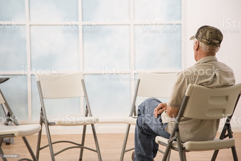 Lonely senior man waits for support, counseling group to arrive. stock photo